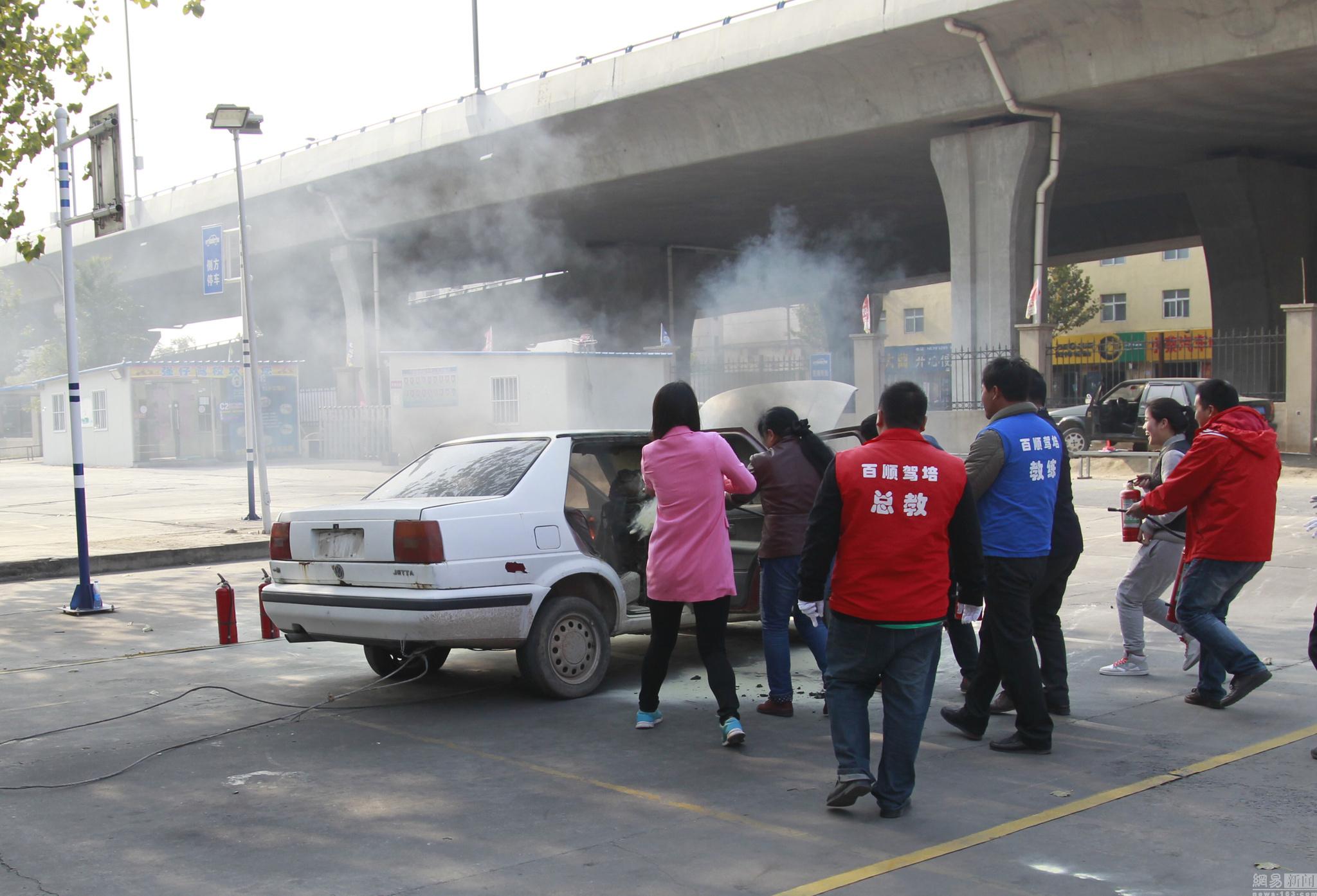 图为驾校学员学习灭火技能。